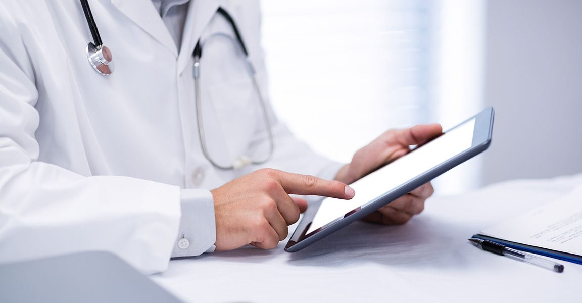 Mid section of male doctor holding digital tablet